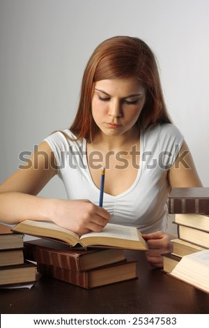 A young pretty student writing on books on the table on a white background - stock photo