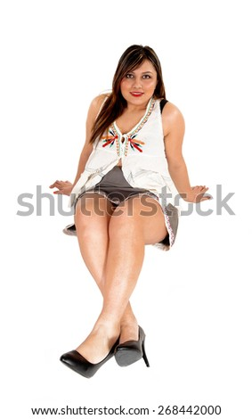A young pretty woman in a short grey skirt and high heels sitting on the floor, isolated for white background.