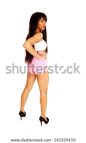 A young pretty woman in pink shorts, white top standing for white background from the back, showing her gorgeous figure.