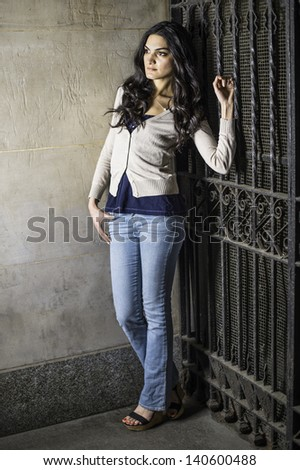 A young pretty woman is leaning on a metal gate and into deeply thinking/Deeply Thinking - stock photo