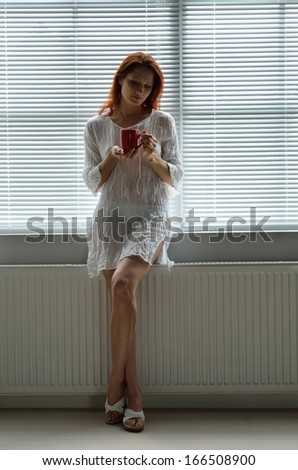 A young pretty woman is standing on the window at home. It is closed with jalousie. She is leaning a radiator and holding a cup.