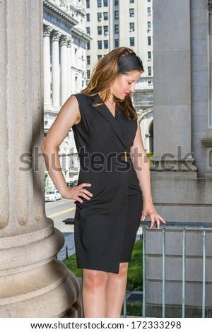 A young pretty woman is standing outside an office building, a hand resting on her hips, a hand touching railings, looking down and thinking. / Thinking Outside  - stock photo