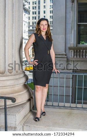 A young pretty woman is standing outside an office building, a hand resting on her hips, a hand touching railings, looking up, relaxing and thinking. / Thinking Outside  - stock photo