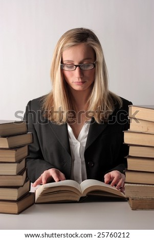 A young pretty woman reading a book and sitting on a table above a white background - stock photo