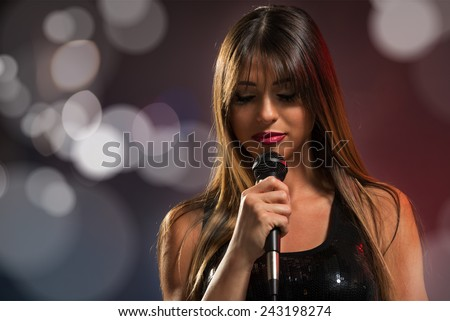 A young pretty woman singer, singing with eyes closed, holding a microphone.