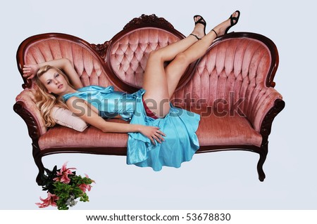 A young pretty woman with long blond hair and a light blue dress, lying on a pink sofa, shooing her nice long legs in high heels on light blue background.
