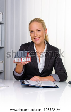 a young real estate agent with a model home in her office. - stock photo