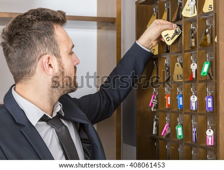 A young receptionist taking a key at the reception.