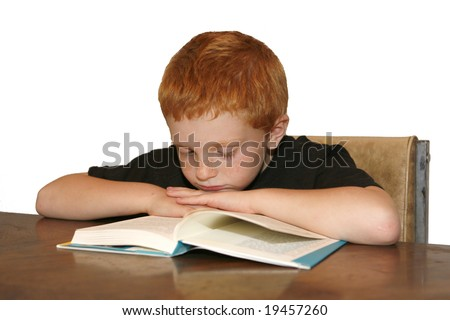 A young red haired boy falling asleep while reading a book.