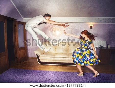 A young red-haired woman engages her super powers while getting in a fight with her man. - stock photo
