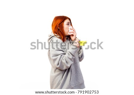 A young red-haired woman in a gray sweatshirt is sick, sneezes and drinks from a large transparent cup of an antiviral agent for treatment on a white isolated background