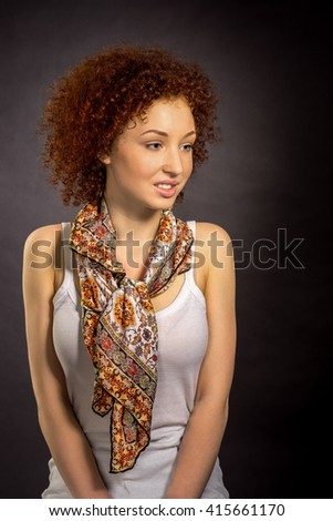 A young red haired woman in a neckerchief leaning against a gray wall - stock photo