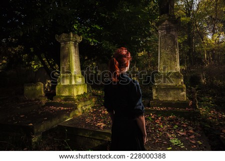 A young redhead woman is standing in a cemetery - stock photo