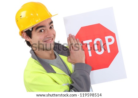 A young road worker holding a stop sign. - stock photo