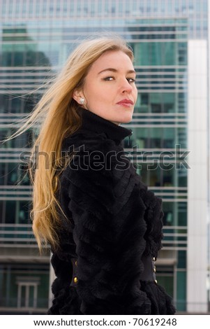 a young Russian woman wearing a fur coat in the city.