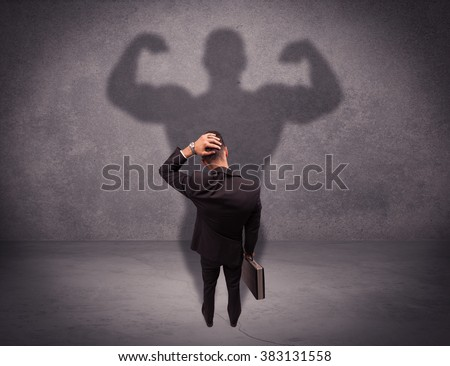A young salesman standing with his back, looking at his musculous shadow reflecting on the wall concept - stock photo