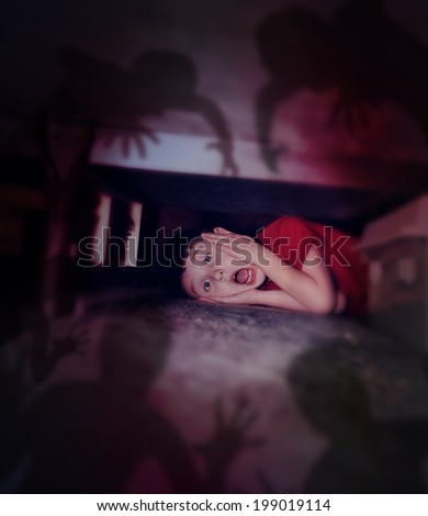 A young scared boy is hiding under a bed looking at black scary monster ghosts in fear for a bedtime or evil concept. - stock photo