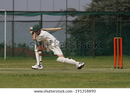 A young school boy is playing a square drive shot with a beautiful follow through finishing it perfectly. - stock photo