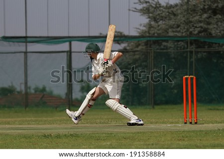 A young school boy playing cricket is tepping out on the front foot attacking the ball - stock photo