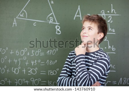 A young schoolboy standing near the blackboard and thinking about something. - stock photo
