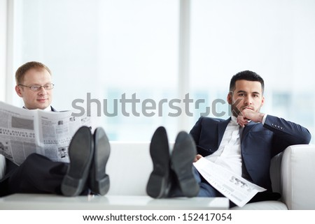 A young serious businessman with newspaper looking at camera with his colleague reading news near by - stock photo