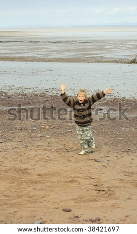 a young seven year old blonde boy plays with a ball on the beach
