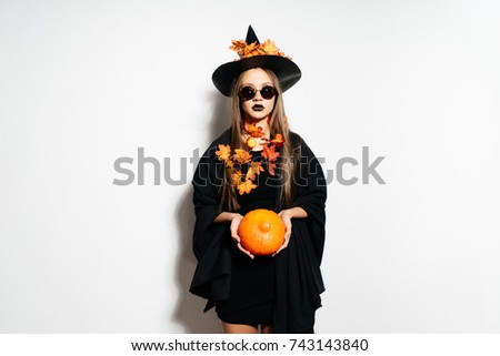 a young sexy gothic girl celebrates halloween, dressed in a witch, holds a pumpkin in her hands