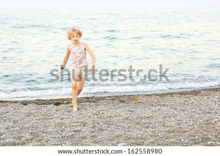 A young, short blond hair, girl, running and playing on a rocky Lake Ontario beach at dusk, at Centennial Park, Hamilton, Ontario, Canada.  Motion visible on hands and arms. - stock photo