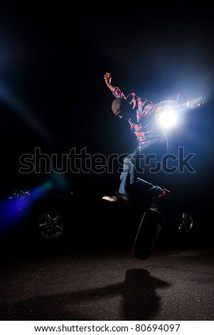 A young skateboarder doing jumping and kick flip tricks under dramatic rim lighting with lens flare. - stock photo
