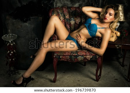 A young, slim, attractive blond woman wearing sexy blue bra an panties reclining provocatively on chair. - stock photo