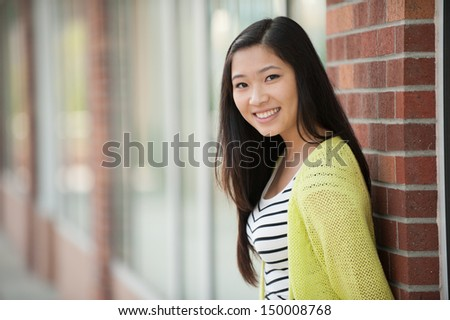 A young smiling beautiful Asian girl leaning against a wall - stock photo