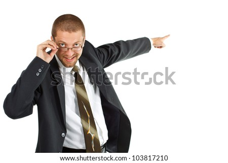 A young smiling businessman with suit and tie is looking into the camera, touching his glasses, and pointing with other hand,with forefinger backwards - stock photo