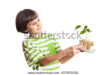 A young smiling child is holding a sprout of cucumber - stock photo