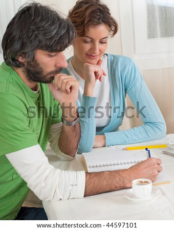 A young smiling couple making plans or studying at their dining room table.