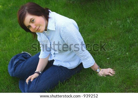 a young smiling girl sitting on a grass. - stock photo