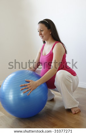 A young smiling pregnant woman in a pink shirt doing a squatting exercise with a blue fitness ball while standing up. - stock photo