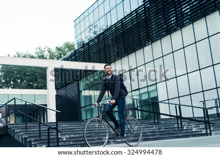 A young smiling stylish businessman riding a bicycle while going to work.