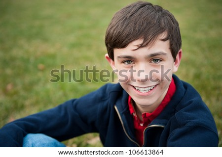 A young smiling teenage boy outside on grass - stock photo