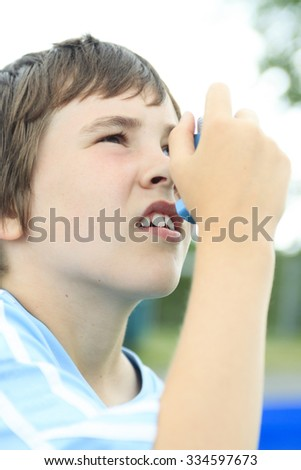 A young soccer player taking his asthma inhalator