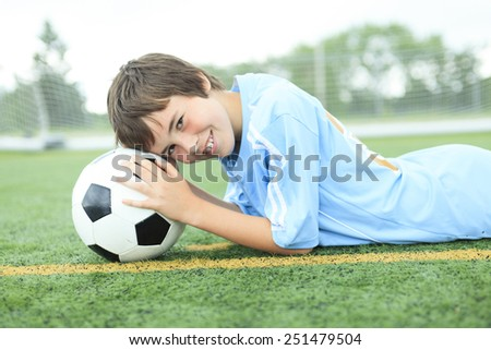 A young soccer player with ball on the field - stock photo