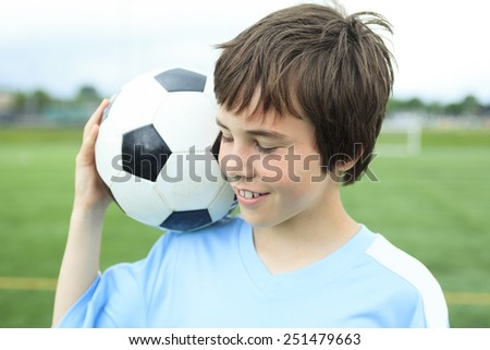 A young soccer player with ball on the field