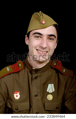 a young Soviet soldier poses for the photographer on the black background - stock photo