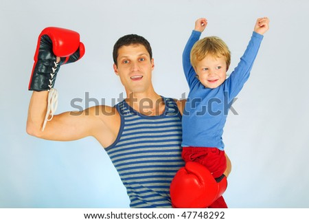 A young sporty men in a red boxing gloves with son