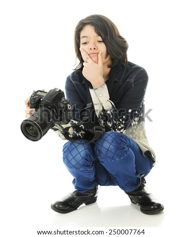 A young squatting photographer carefully studying the image in the back of her camera.  On a white background. - stock photo