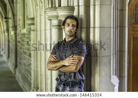 A young strong handsome guy is standing by a old fashion wall, crossing arms and thoughtfully looking away. / Portrait of Young Guy - stock photo