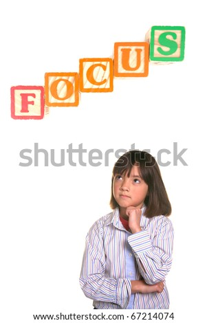 A young student strikes a focused posture with word block above. - stock photo