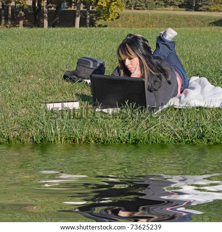A young student using her laptop computer while laying in the grass on a nice day. - stock photo