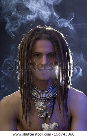 a young stylish man with dreadlocks and a lot of silver jewelry smoking a cigarette, blue filter effect  - stock photo