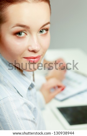 A young successful businesswoman sitting at the table - stock photo