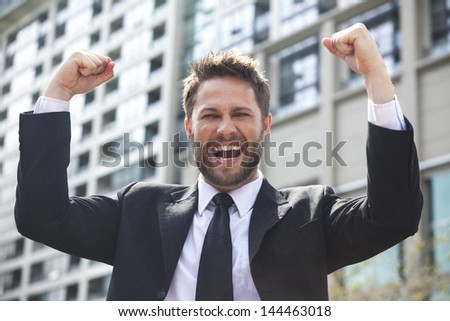A young successful man, male executive businessman arms raised celebrating cheering shouting in front of a high rise office block in a modern city